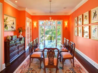 Vibrant Orange Dining Room With Traditional Wood Buffet and Long Glass Dining Table