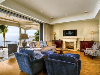Spacious Living Room With Blue Velvet Arm Chairs and Open Wall Connecting to Covered Balcony