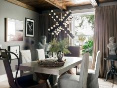 This wow-worthy dining room has a transitional style and moody European look, with curated art on dark walls and a dramatic chandelier.