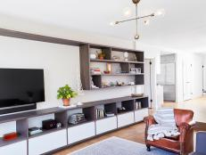 Long Modern Shelving Creating Stylish Entertainment Center in Bright Living Room With Brown Leather Armchair