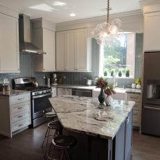 modern bubble chandelier over diamond cut marble countertop island and vertical subway tile kitchen backsplash