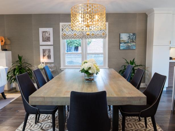 Decorative Gold Light Fixture Over Wood Dining Table and Midcentury Modern Black Dining Chairs