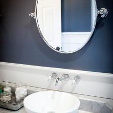 White Contemporary Vessel Sink on Gray Marble Countertop Beneath Dark Navy Accent Wall in Bathroom