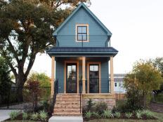 Bold Dark Green Vintage Tiny Home with Wrap Around Brick Skirt ,Unpainted Wood Columns, Iron railing and Metal roof