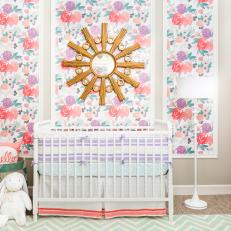 A Stylish Nursery's Floral Panels and Gold Sunburst Mirror Frame the Crib