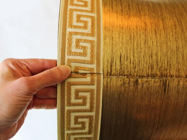 Easily turn an old trashed lampshade into a trendy treasure just by attaching upholstery tape trim.