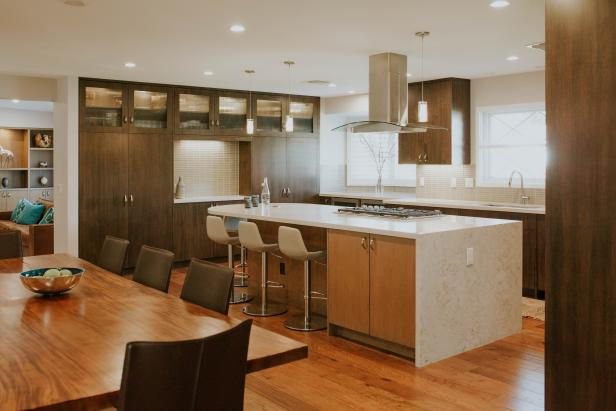 Open Contemporary Kitchen and Dining Room With Large White Countertop Island, Full Wall Cabinetry and Neutral Color Scheme