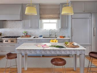 Transitional Kitchen Featuring Gray and White Chevron Backsplash, Marble Topped Table and Wood Stools