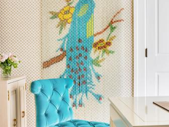 Contemporary Sitting Space With Vivid Pop of Blue on Tufted Chair and Tropical Peacock Wall Decor Over Textured Carpet