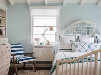 Pastel Blue Walls in Cottage Bedroom With White Bed With Blue Linen Accents, Blue and White Striped Chair and Light Wood Furniture
