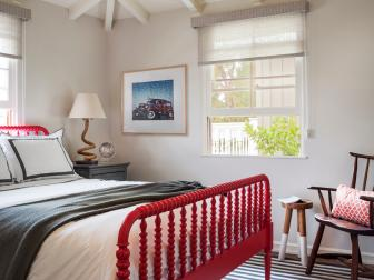 Country Bedroom With Bright Red Bed Frame, Black and White Bed Linens and Simple Wood Chair