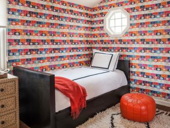 Contemporary Bedroom With Colorful Penguin Books Wallpaper, Black Twin Bed Frame, and Orange Leather Floor Pillow