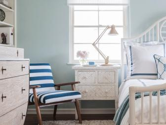 Airy Coastal Bedroom With Horseshoe Shaped Dresser, Pale Blue Walls, Exposed Ceiling Beams and Striped Chair