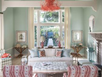 Mint Green Shabby Chic Living Room With Coral Chandelier, Large Tufted Coffee Table and Wavy Striped Arm Chairs