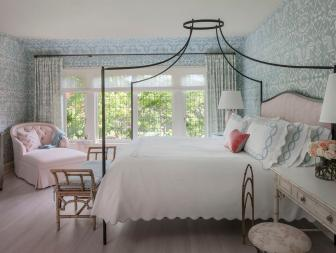 Feminine Shabby Chic Bedroom With Iron Canopy Bed Frame, Blue Patterned Wallpaper and Plush Pink Chaise