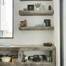 Gray Stone Kitchen Countertop and Shelf Structure With Matching Floating Shelves Over White Wall