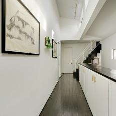 Bright, White Hallway With Dark Hardwood Floor and Countertop Over White Cabinets With Gold Handles