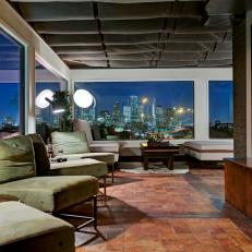 Dim, Stylish Dining Area With Skyline View, Plush Green Chairs and Red Stone Flooring