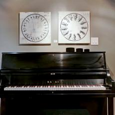 Black Piano in Front of Gray Wall With Black and White Wall Art