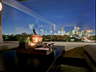 Romantic Dining Setting With City Line Window View, Dark Table With Bench Seating and Candle Centerpiece