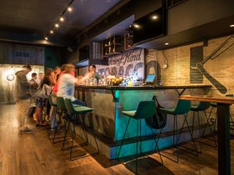 Hip, Casual Bar With Green Contemporary Barstools, Painted Brick Accent Wall and Built In Upper Cabinetry