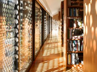 Metal Cutout Sunshades Allow Dappled Light Into Second Floor Library