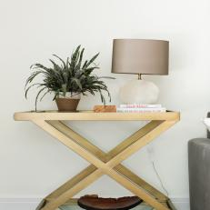 gold end table and white textured lamp add glamour to midcentury modern living room