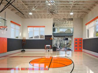 Indoor Basketball Court With Orange Accents, Charcoal and Orange Wall Pads and High Beamed Ceilings