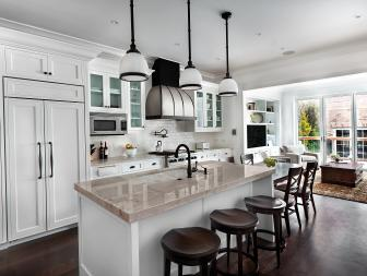 Open, Traditional Eat In Kitchen With Blended Refrigerator, Pendant Lights, and Wood Barstools At Neutral Marble Bar