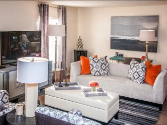 Modern Living Space with Pops of Orange and Black and White Pillows and Rug