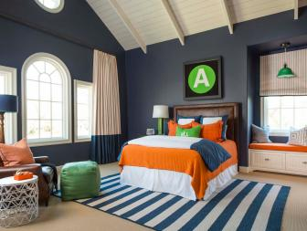 Spacious and Bold Teen Bedroom With Bright Orange and Green Accents Against Dark Blue Walls