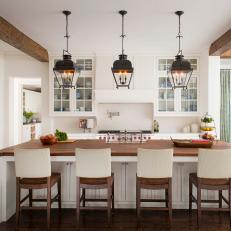 Lantern Pendant Lights Over Large Eat In Kitchen Island With Wood  Countertop And Wood Chairs With Neutral Back Slip Covers