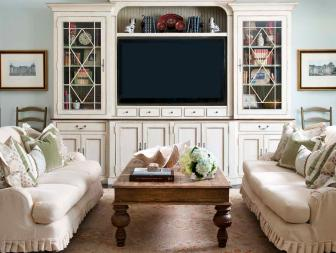 Cozy Shabby Chic Family Room Featuring Neutral Sofas With Ruffles Skirts and Large Entertainment Center With Mullion Cabinets