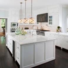 Bright Transitional Kitchen With White Marble Countertops And Cabinets Over Dark Hardwood Floor