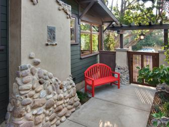 Outdoor Concrete Walkway With Cherry Red Bench, Stone Based Columns and Wood Gate With Small Pergola