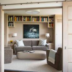 Modern Library Concealed by Barn Doors to Create a Reading Nook
