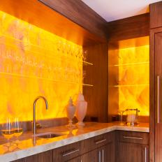 Honey Onyx Wet Bar with Back Lighting and Floating Star Fire Glass Shelving is Focal Point in Living Area