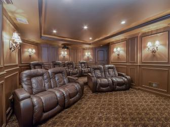 Single and Double Brown Leather Seats in Home Theater With Patterned Carpet and Lampshade Sconces