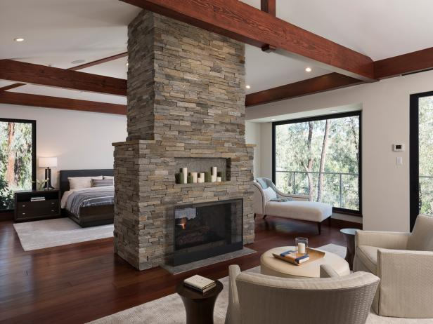 stone double fireplace in contemporary master bedroom - Design Bedroom