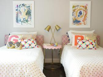 Pink and Gold Girl's Bedroom With Colorful Pillows and Paintings