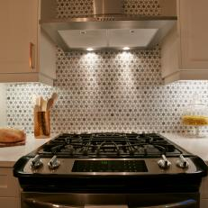 circle pattern tile backsplash behind stainless steel range hood and white cabinetry with rose gold handles