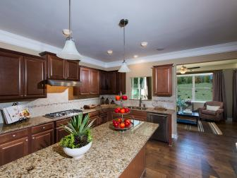 Dark Wood Kitchen with Tan Marble Countertops and Light Colored Tile Backsplash