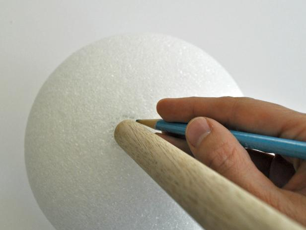 Align wooden dowel onto foam ball and trace around dowel with pencil. Use knife to carve out circular shape 1 inch deep. Hot glue end of dowel and place into hole of foam ball. Add additional glue to fill in around edges of hole. Repeat steps on other foam ball. Tip: Use coolest setting on hot glue gun to void melting foam. Paint barbell with black acrylic paint. Tip: Due to the porous nature of the foam ball, pour paint onto ball, then gently brush it around to coat all textured areas. Do not attempt to use spray paint; spray paint melts foam.