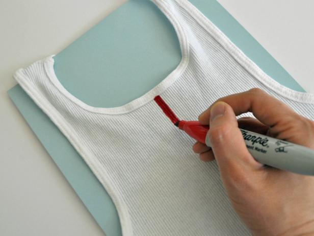 Place paper inside shirt to avoid marker bleeding onto other side. Draw stripes on tank top with permanent marker or fabric marker. Use ribs of shirt as a guide and pull marker along fabric rather than pushing it.
