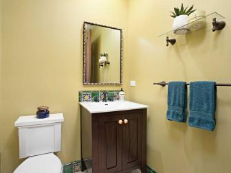 Yellow Mediterranean Powder Room With Blue Towels