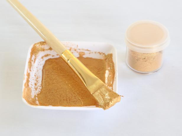 Combine gold luster dust and drops of vodka in a small condiment cup and stir until a thin gold paint consistency is achieved.  Load a stiff bristle brush with the paint.