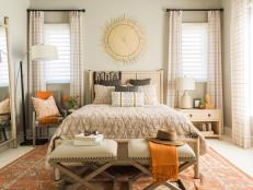 This welcoming guest suite with vibrant bursts of orange accents and earthen design details creates a relaxing retreat for visitors.