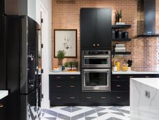 Defined by bold black cabinetry and oversized light fixtures, the high-tech kitchen offers space for both food prep and entertaining.