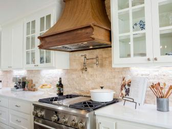 Renovated Kitchen With Natural Stone Backsplash and Wood Range Hood