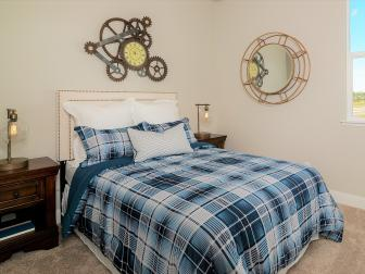 Guest Bedroom With Blue Plaid Bed Linens and Clock Gear Art